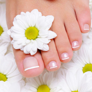 female hand with beautiful french manicure on the pure and clean foot
